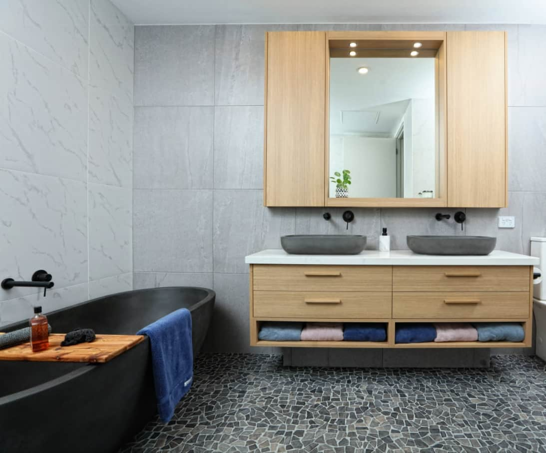 Top Reasons to Invest in a New Bathroom. Faux concrete tile, wooden furniture for two and black egshell bathtub for maximum chic