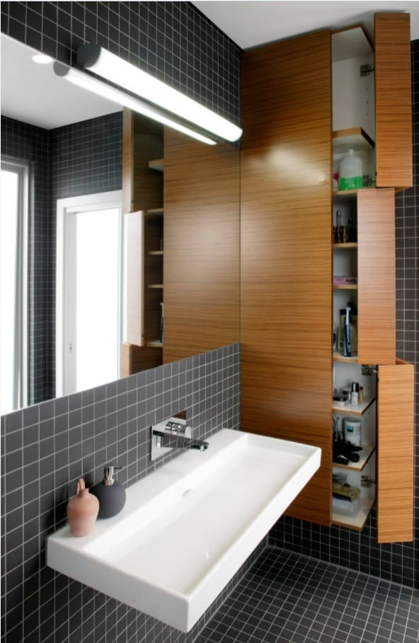 Top Reasons to Invest in a New Bathroom. Dark Metro tile with white grout, multifunctional cabinet and large mirror