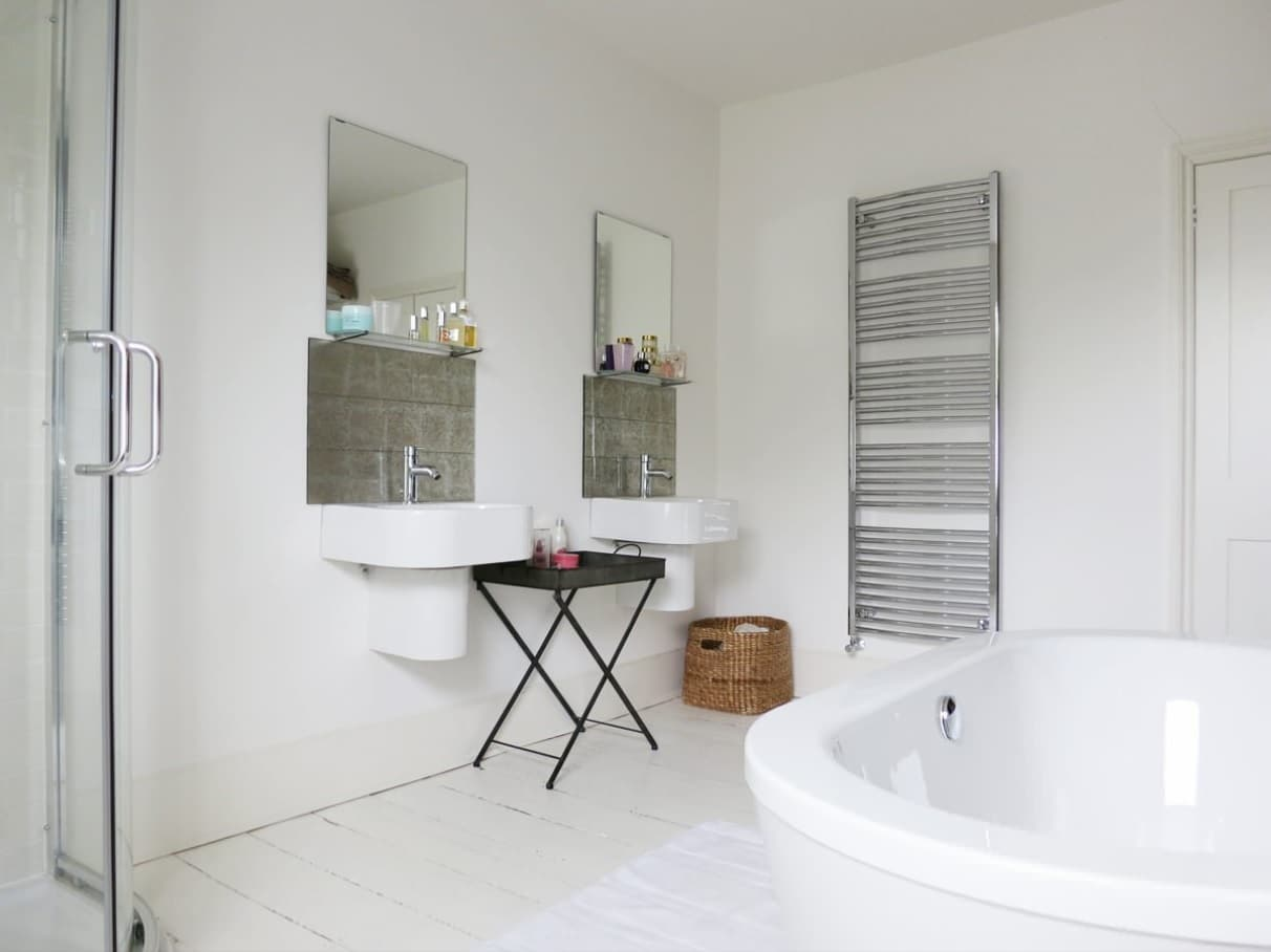 Top Reasons to Invest in a New Bathroom. Steel towel rail in white minimalistic interior