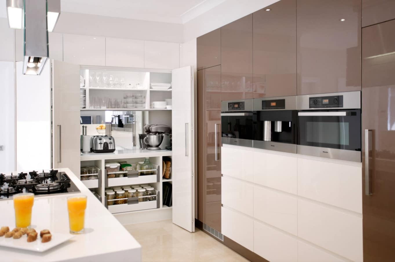 How to Make Your Kitchen Look more Expensive. Brown chocolate color and glossy surfaces along with hidden storage space for cookware