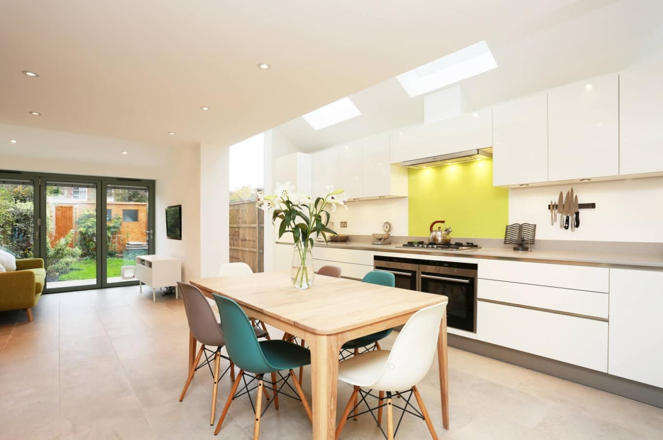 How to Make Your Kitchen Look more Expensive. Large minimalistic area with a dining zone, joyful yellow backsplash at the hob and full of light through skylights and LED fixtures