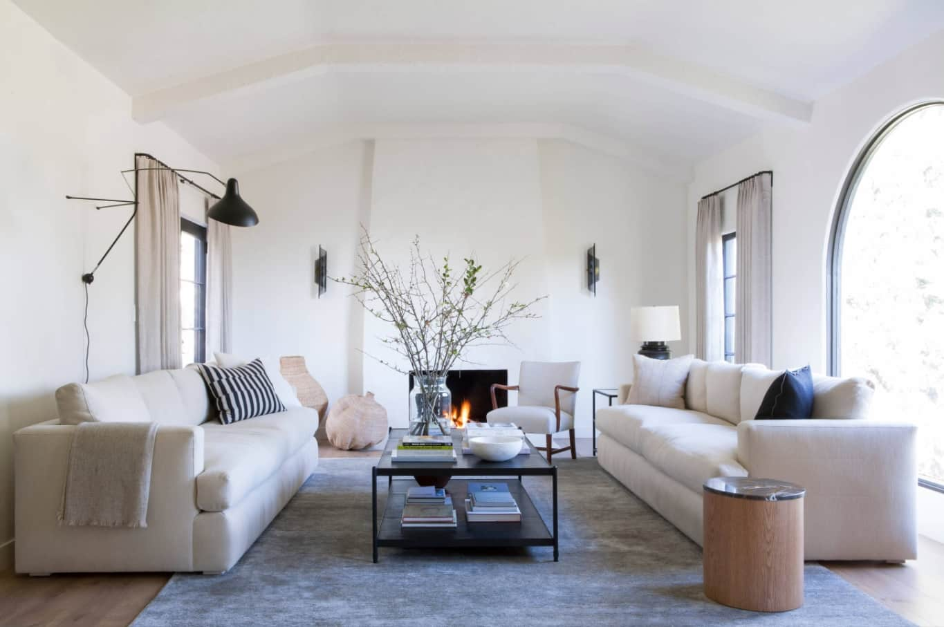 The Best Tips for Living Room Decoration. Simple casual design with black metal framed coffee table, two white sofas and even a real fireplace