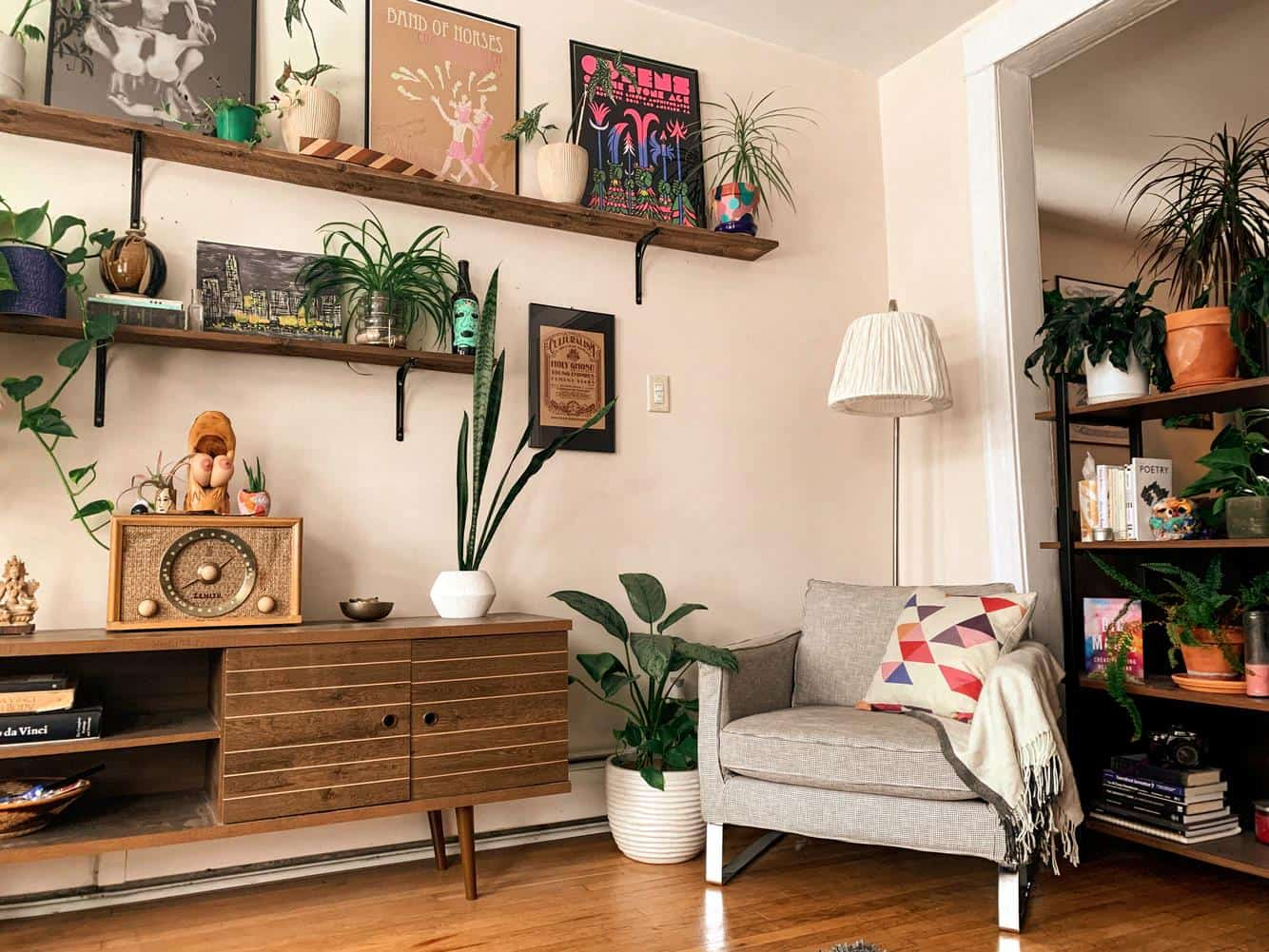 How To Boost Your Living Room's Beauty On A Budget. Ecological casual interior decoration with plants in pots on the cupboard, shelves and even the floor