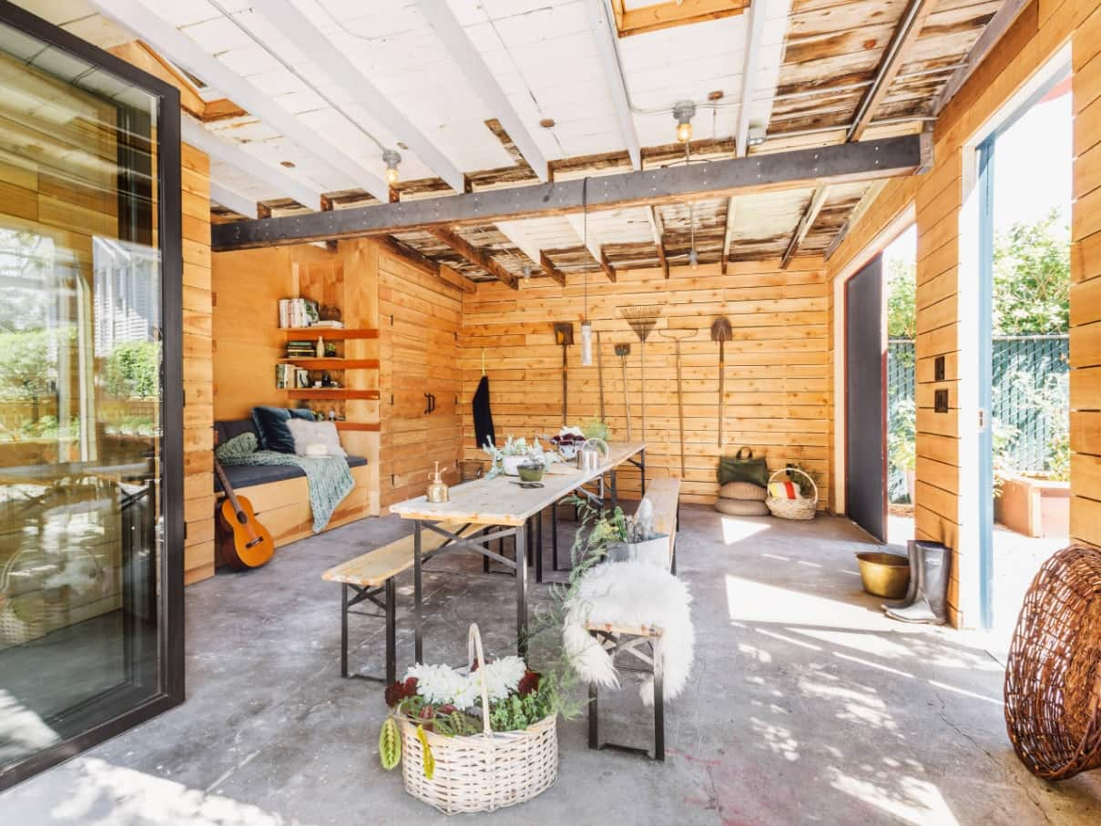 The Best Way to Clean Your Garden Shed. Well-organized interior with concrete floor and light wooden wall finish in Scandi style