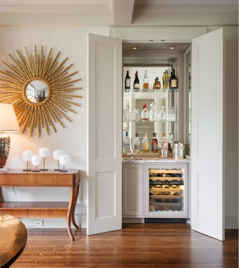 How To Create the Home Bar of Your Dreams. Starburst mirror and hidden bar as a decoration for casual styled interior with wooden floor and table