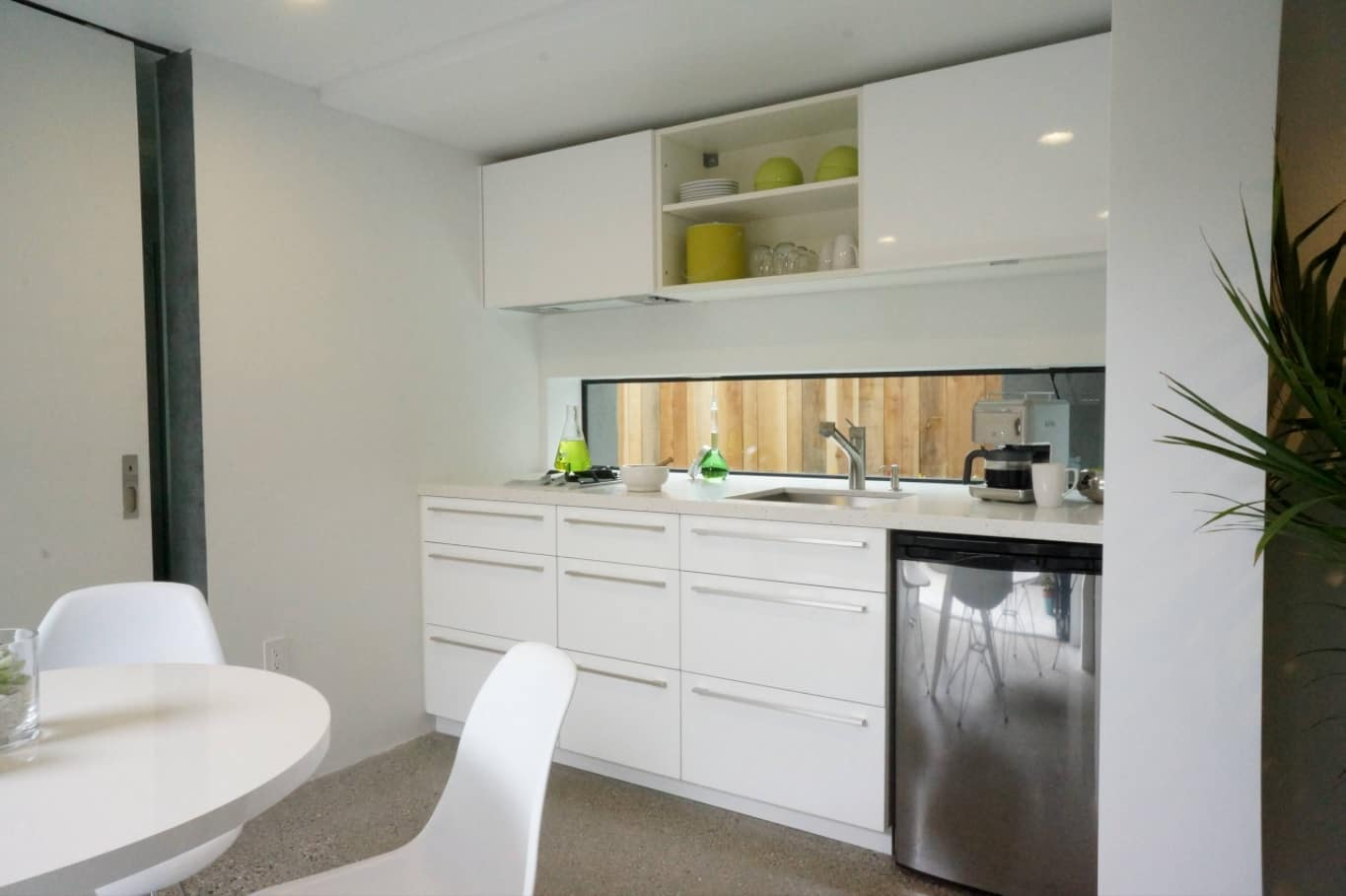 What Separates A Kitchen From A Kitchenette? All-white interior with small improvised kitchen zone and small fridge