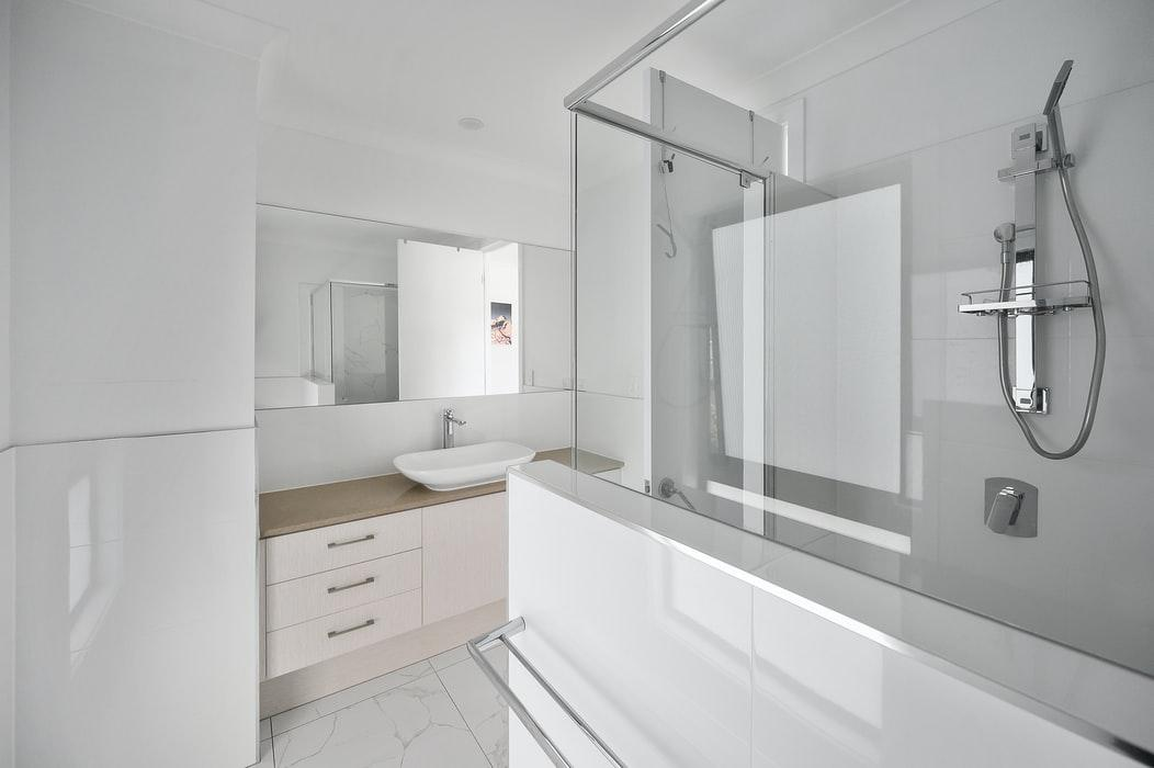 How to Fix Moisture Problems in Your Bathroom. Totally white bathroom with glass partitions and mild brown wooden vanity in modern style
