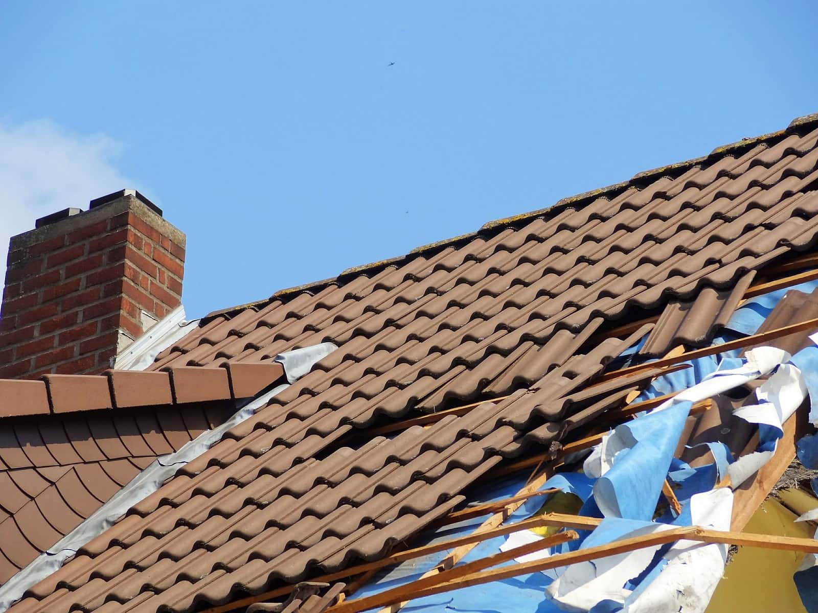 4 Signs That It's Time To Replace Your Roof. Old ceramic roof tiles and partly dilapidated covering