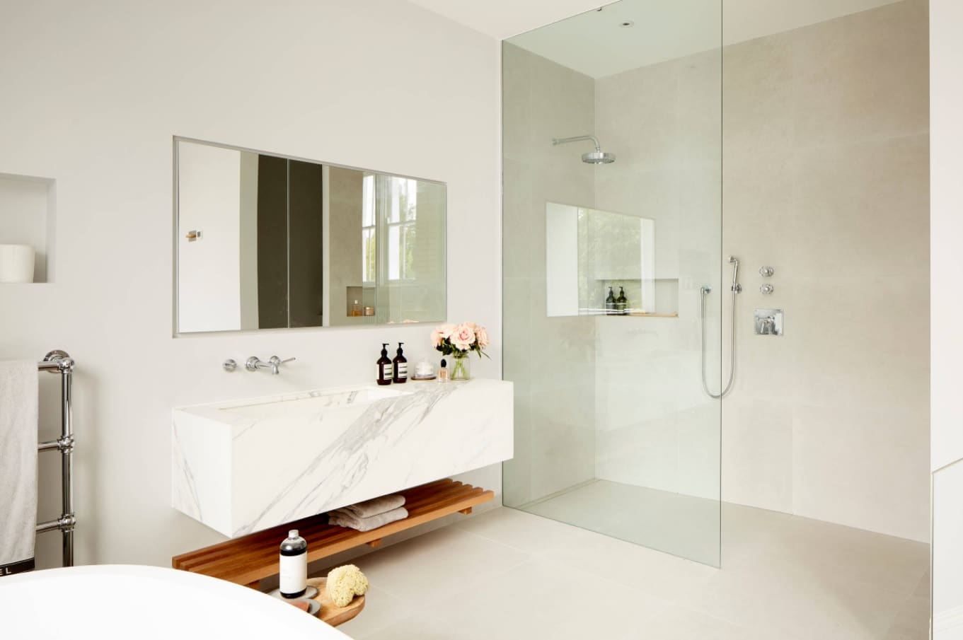 Bathroom Necessities_ 9 Things You Need to Have in Your Bathroom. Stylish contemporary bathroom in pastel creamy tones with hovering vanity and glass shower screen