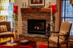 7 Ways To Give Your Home A Warm And Comfy Atmosphere. Christmas decorated fireplace with wooden mantelshelf and stone finishing