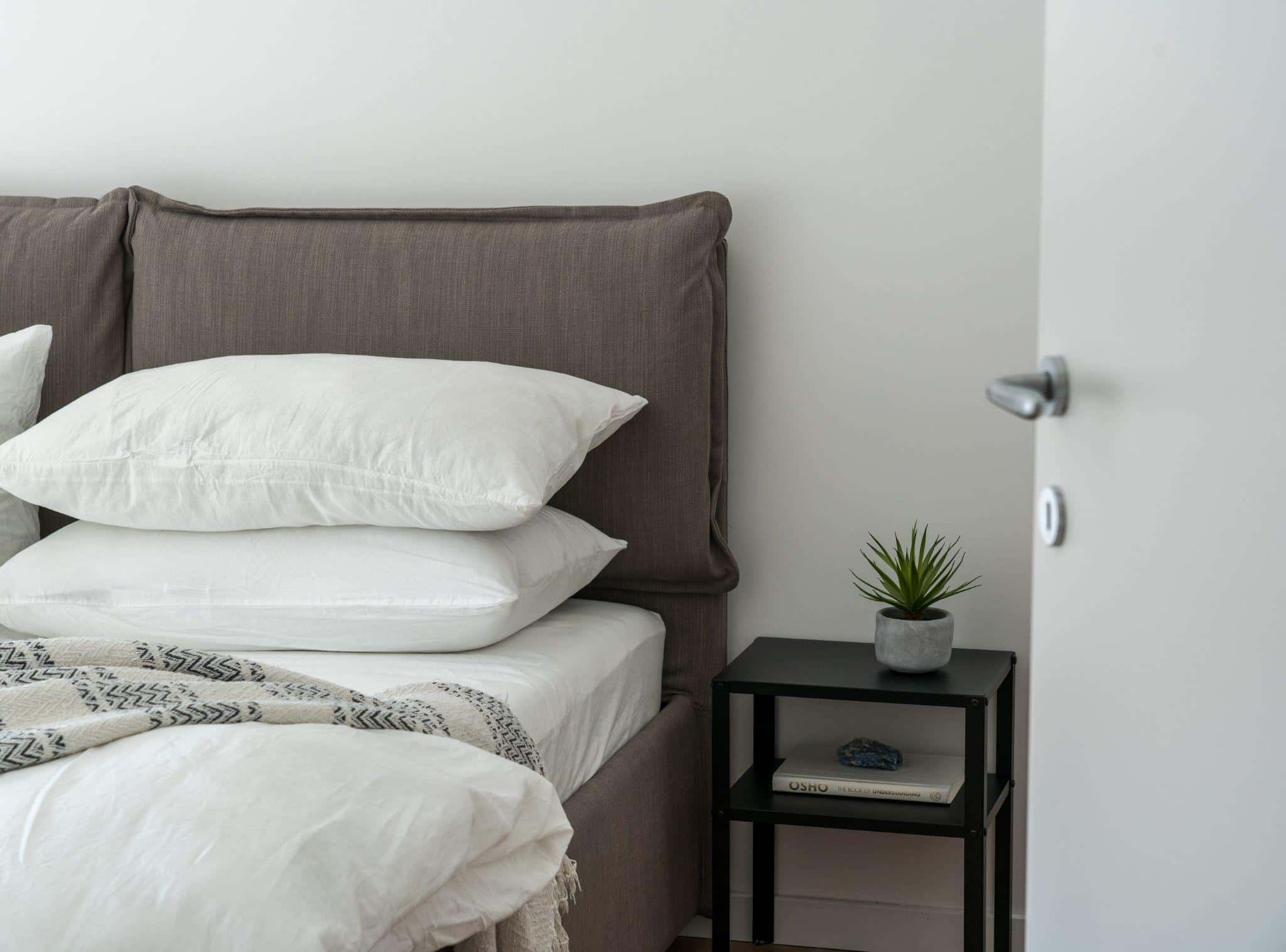 How To Choose A Perfect Bedding: Useful Tips. Reserved interior decoration in casual style with dark bedding and light walls