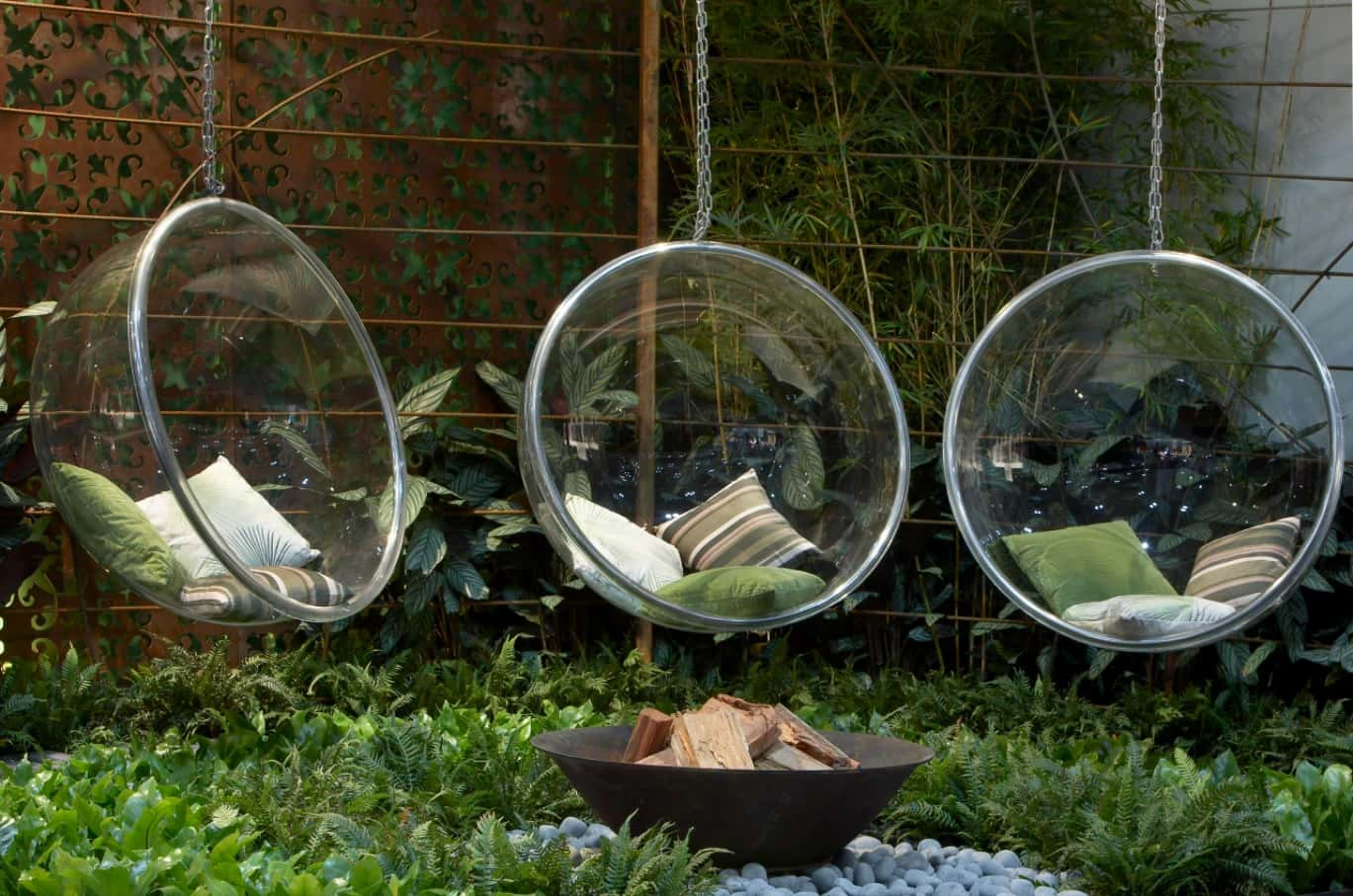 Make Your Garden Your Favorite Hangout Spot. Bubble plastic hanging chairs at the backyard around the fire cauldron