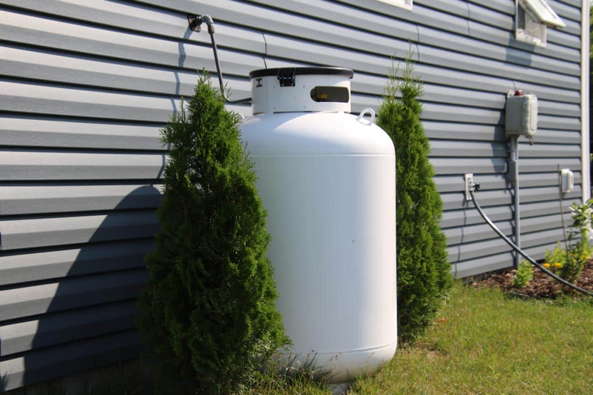 How to Hide That Ugly Propane Tank. Masterfully hidden tank among the shurbs at the fence