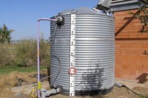 Why Should You Invest in Rainwater Tanks for Your Home? Metal rainwater tank with tags and plumbing