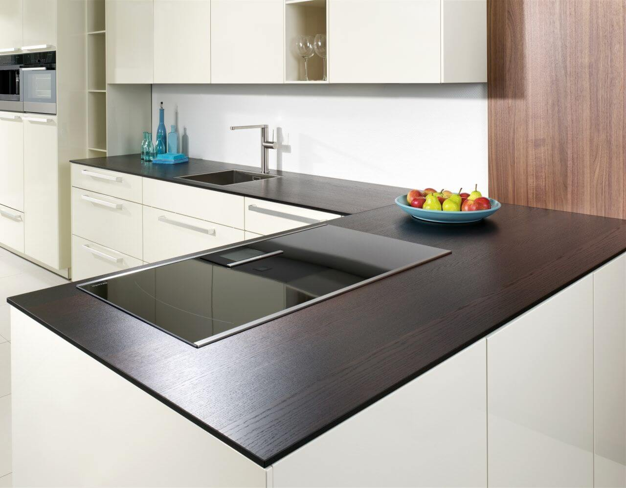Black wooden top and white facades of the furniture for modern designed kitchen