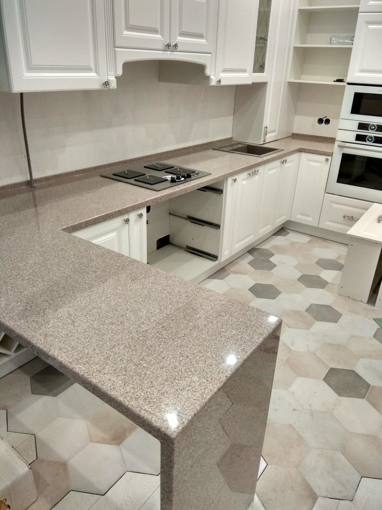 Mosaic hexagonal tile for the floor and marble topped furniture in the light pastel kitchen