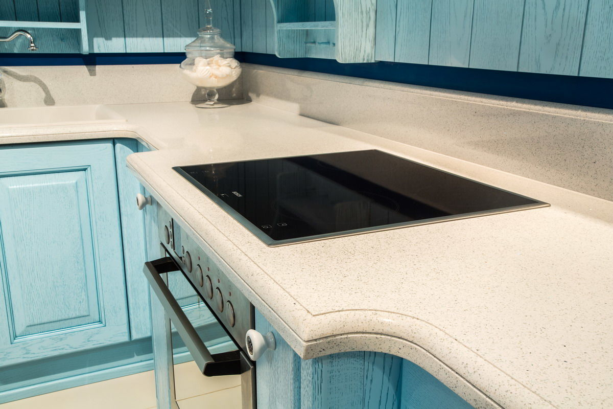 Wavy protruding edges of the white grained concrete top in the turquoise colored kitchen