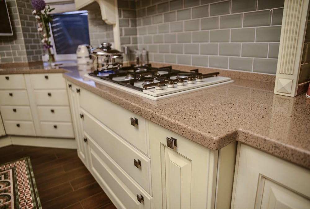 Classic kitchen interior with gray metro tile backsplash and pastel colored cabinets