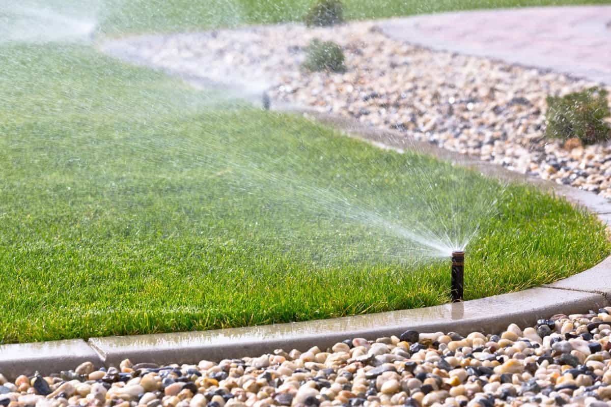 3 Steps to Landscape a Garden from Scratch. Sprinklers around the trimmed lawn