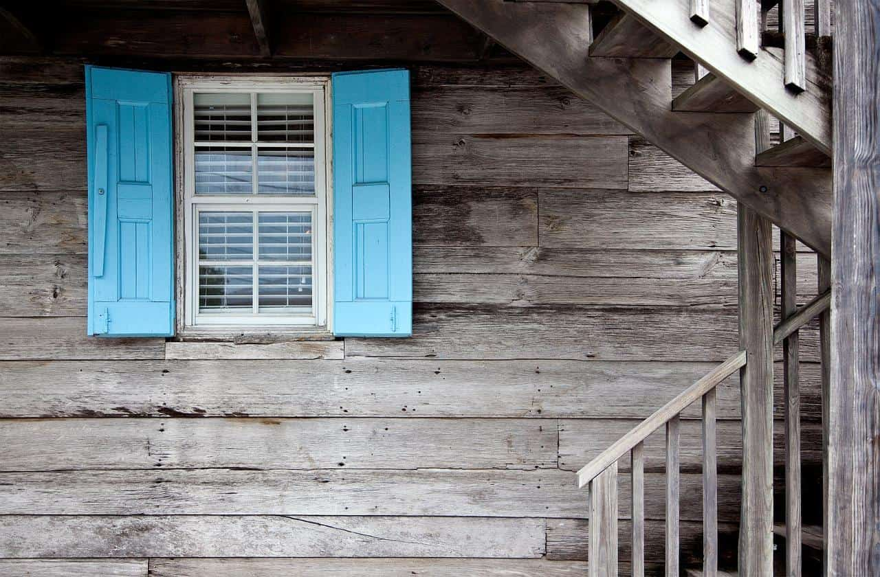 Why It's Important To Maintain And Clean Your Windows. Suburban natural wood trimmed house with accent blue shutters