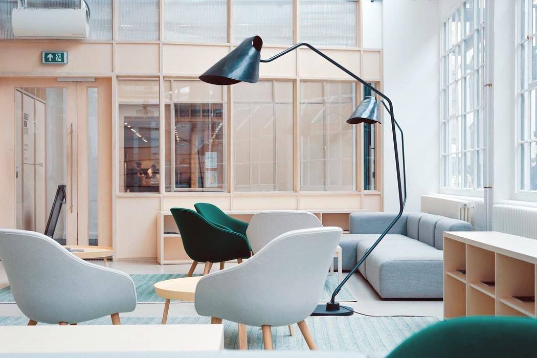 Portable Walls in the Interior of the Modern Apartment. Wooden and glass wall for delimiting the large Scandinavian styled space with large floor lamps and plastic chairs