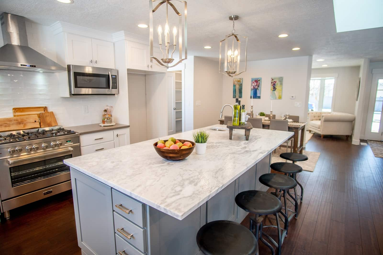 5 Reasons You Should Remodel Your Home Now. Chalet touch of the contemporary styled kitchen with large marble-topped central island and black round bar stools