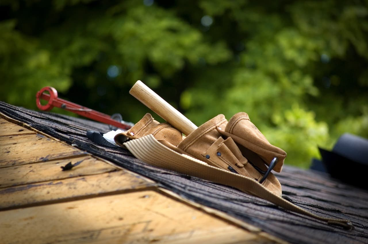 Choosing the Best Roofing Option for a Tiny Home. Tools for work at the wooden rafters and shingles of the roof