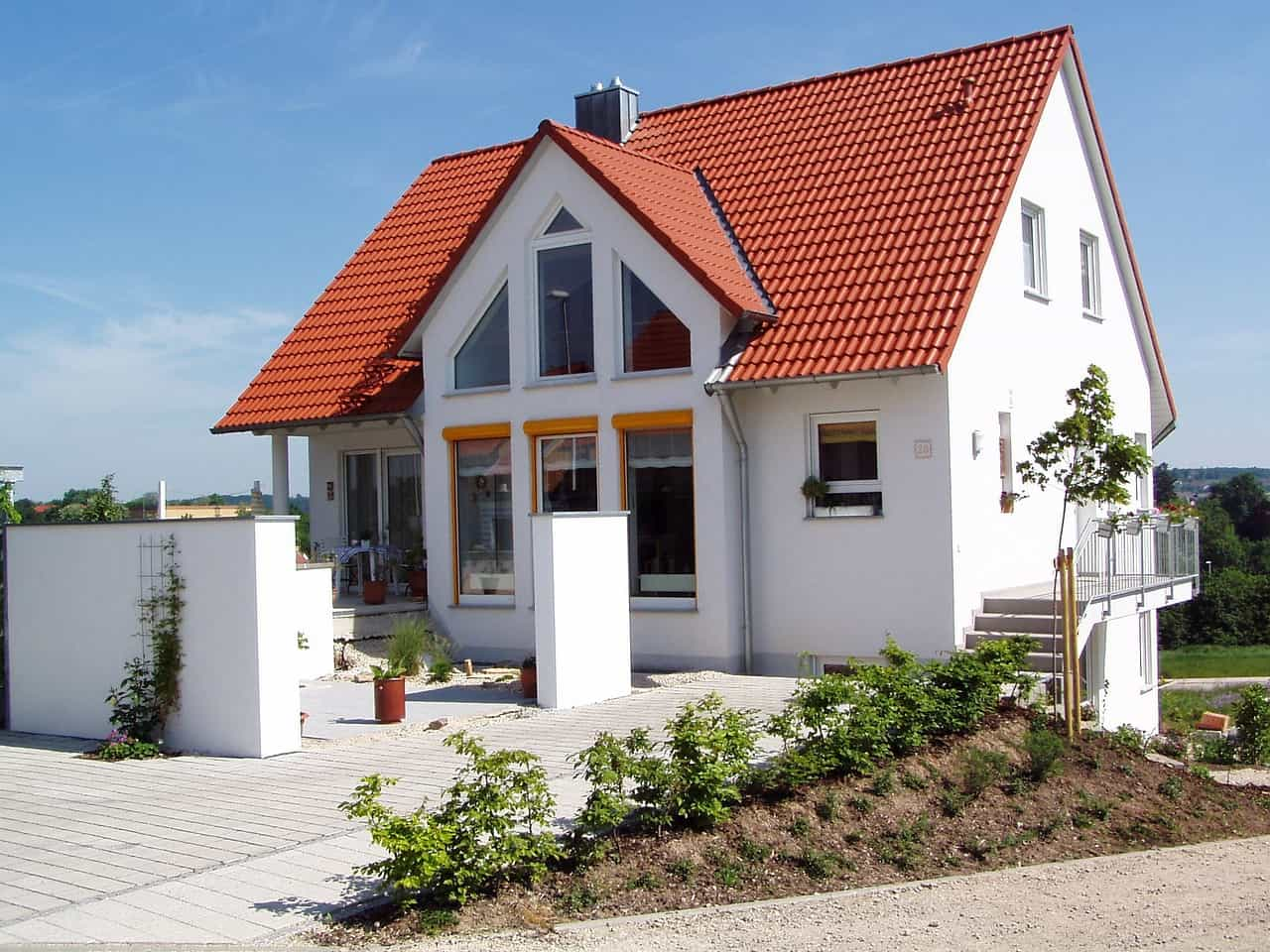 Choosing the Best Roofing Option for a Tiny Home. Nice red ceramic shingles at the top of the white facaded private house