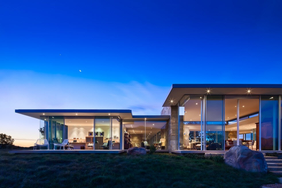 Protruding flat concrete roof and steel basis of the high-tech house with glass panels