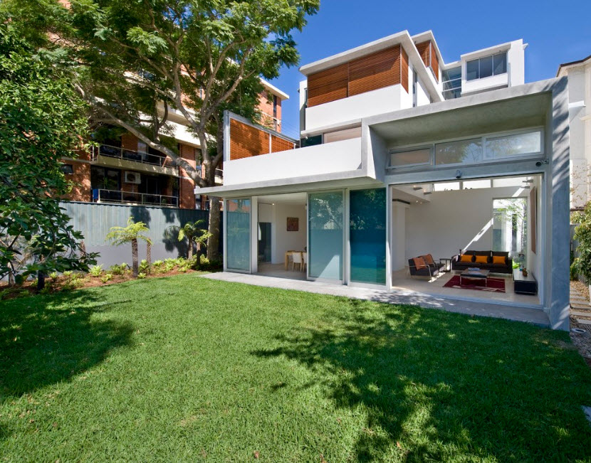 White colored exterior of the high-tech mansion with shady patio zone and a couple of balconies at every story