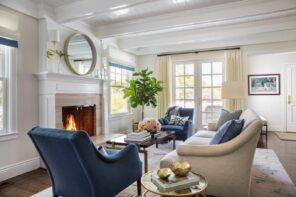 Tips for Decorating with Circular Mirrors. Blue suede furniture and mild brown tones for Classic living room with wainscoting, and the fireplace