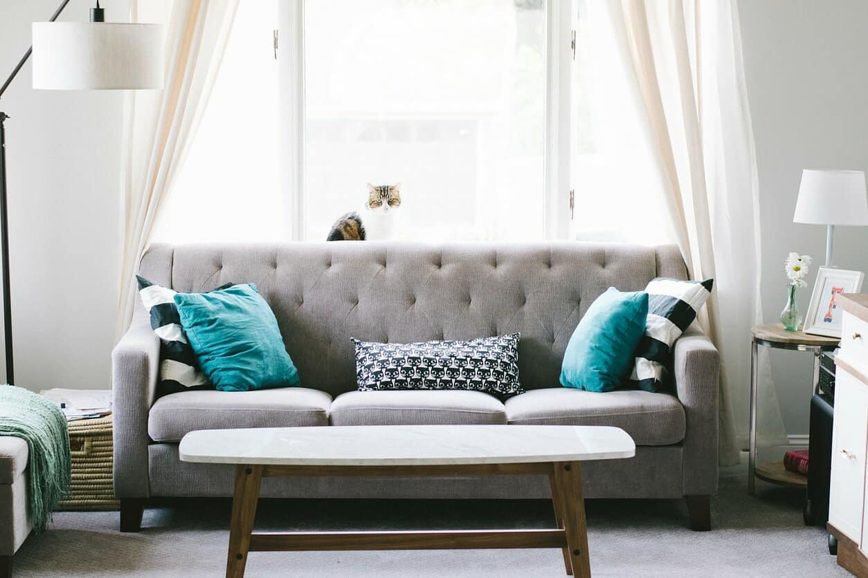 Important Things To Keep In Mind When Choosing Furniture For Your Living Room. Gray quilted sofa with turquoise pillows and gray topped wooden coffee table for the casual-style interior