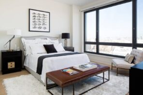 5 Tips For Turning Your Home Into A Rentalю Bright modern styled bedroom with brown leather ottoman